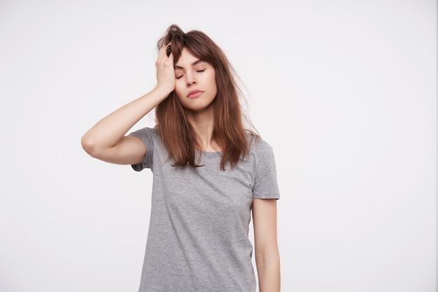 Усталая молодая шатенка с закрытыми глазами, держащая поднятую ладонь на голове, позирует на белом в серой базовой футболке
