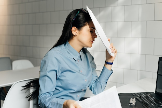 Tired young brunette girl in blue shirt working hard on laptop
