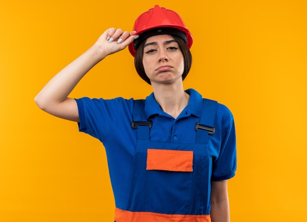 Tired young builder woman in uniform holding safety helmet