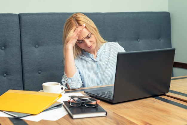 Устал молодая деловая женщина держит голову руками против ноутбука