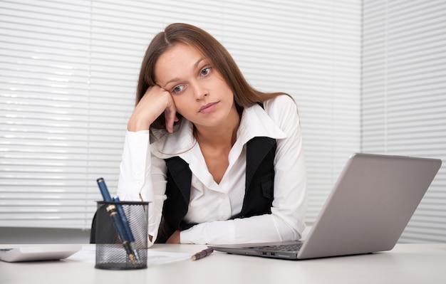 オフィスでラップトップコンピューターで疲れている若いビジネス女性