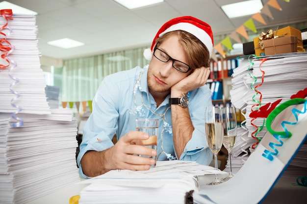 Tired young businessman sitting at workplace among papers on christmas day.