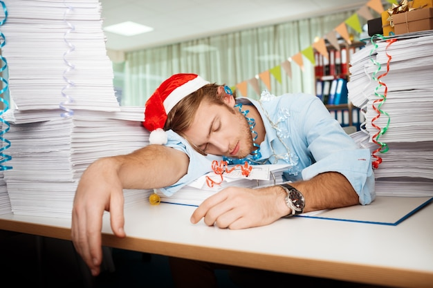 Tired young businessman sleeping at workplace among papers on christmas day.
