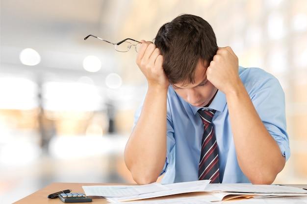 많은 비즈니스 서류와 함께 피곤된 젊은 사업가