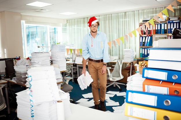 Tired young businessman working in office among papers on christmas day.