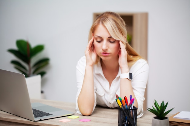 Tired young businesswoman exhausted at workplace in her office