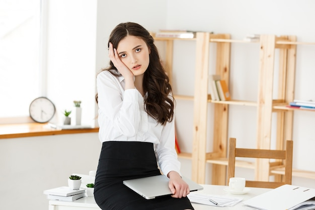Tired young businesswoman suffering from long time sitting at computer desk in office.