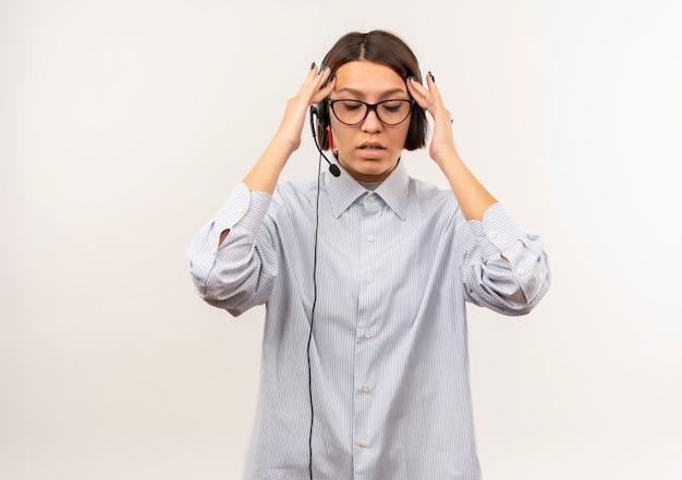 Усталая молодая девушка колл-центра в очках и гарнитуре кладет руки на виски с закрытыми глазами, изолированными на белой стене