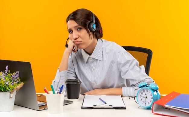 Stanco giovane ragazza della call center che indossa la cuffia avricolare seduto alla scrivania con strumenti di lavoro mettendo la mano sulla guancia isolata sulla parete arancione