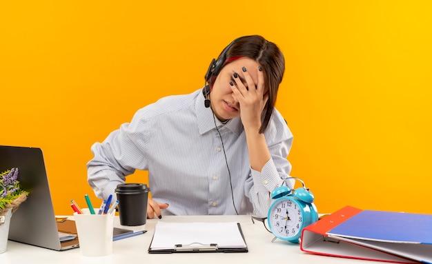 Stanco giovane ragazza della call center che indossa la cuffia avricolare seduto alla scrivania con strumenti di lavoro mettendo la mano sul viso con gli occhi chiusi isolati sulla parete arancione