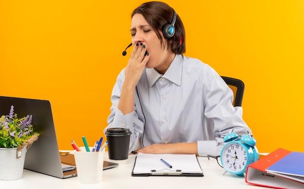 Stanco giovane ragazza call center che indossa la cuffia avricolare seduto alla scrivania con strumenti di lavoro che sbadiglia con la mano sulla bocca e gli occhi chiusi isolati sulla parete arancione