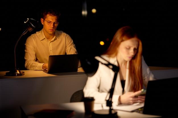 사무실에서 늦은 시간에 일하는 피곤한 젊은 유능한 관리자. 사무실은 어둡다. 남성은 동료들과 컴퓨터 작업을 하고 있습니다. 비즈니스, 마감, 작업 개념입니다. 남자에 초점