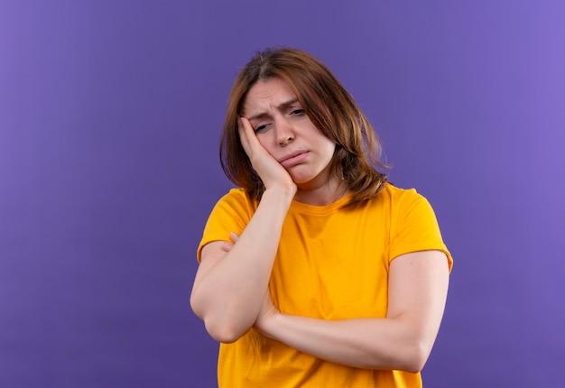 Giovane donna casuale stanca che mette la mano sulla guancia sulla parete viola isolata con lo spazio della copia
