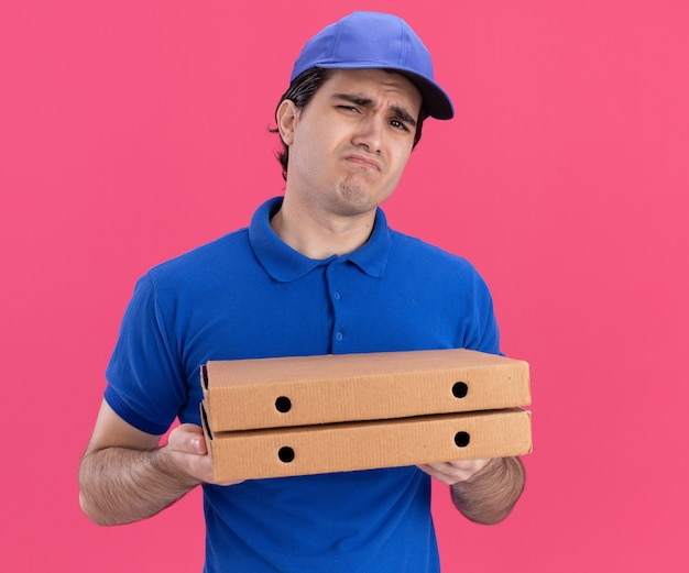 Tired young caucasian delivery man in blue uniform and cap holding pizza packages  isolated on pink wall