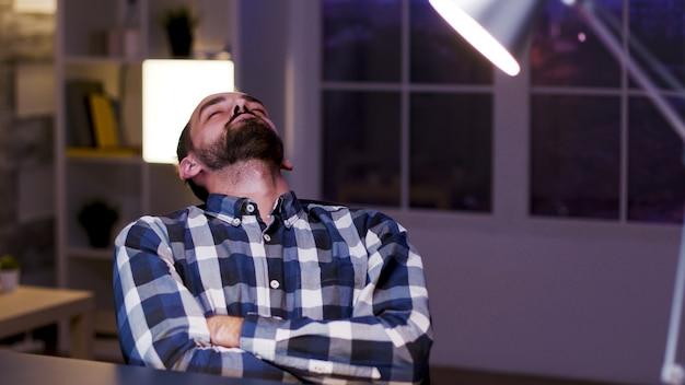 Stanco giovane imprenditore caucasico che dorme sulla sedia nel suo ufficio a casa. uomo d'affari oberato di lavoro.