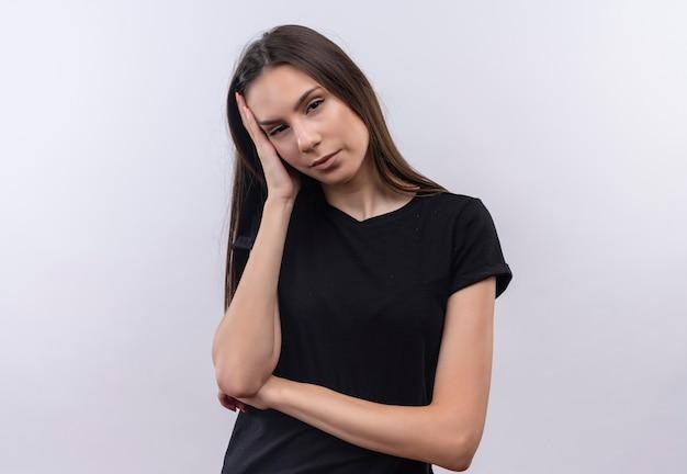 La giovane ragazza caucasica stanca che porta la maglietta nera ha messo la sua mano sulla guancia su bianco isolato