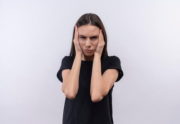 La giovane ragazza caucasica stanca che porta la maglietta nera ha messo le sue mani sulla guancia su bianco isolato