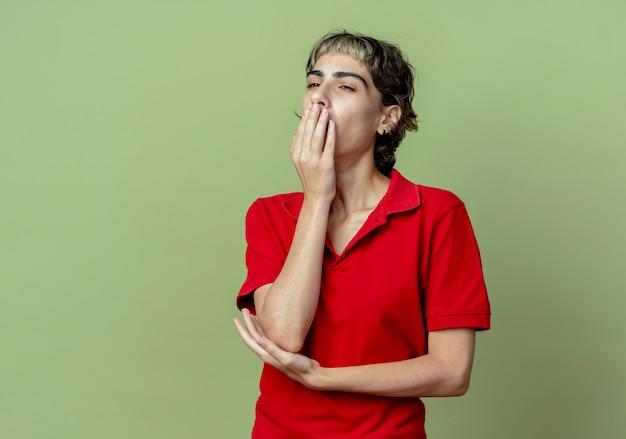 복사 공간 올리브 녹색 배경에 고립 입과 팔꿈치 아래에 손으로 하품 측면을보고 픽시 머리와 피곤 젊은 백인 여자