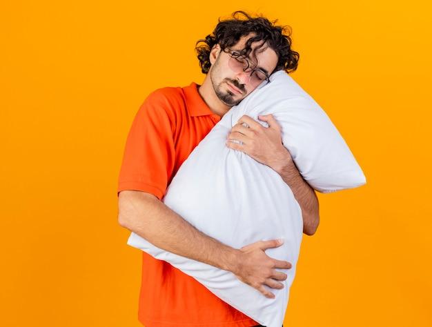 コピースペースでオレンジ色の背景に分離された目を閉じて頭を置く枕を抱き締め眼鏡をかけている疲れた若い白人の病気の男