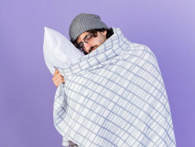 眼鏡の冬の帽子とスカーフを身に着けている疲れた若い白人の病気の人は、コピースペースで紫色の背景に分離された目を閉じて頭を置く枕を保持している格子縞に包まれています
