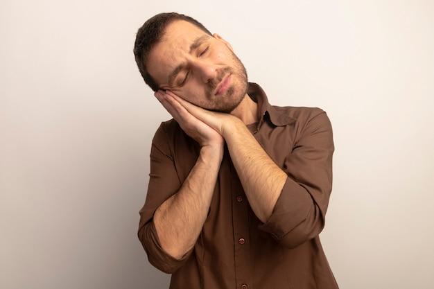 Giovane uomo caucasico stanco che fa gesto di sonno isolato su priorità bassa bianca con lo spazio della copia