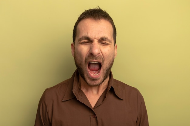 Tired young caucasian man yawning with closed eyes isolated on olive green background