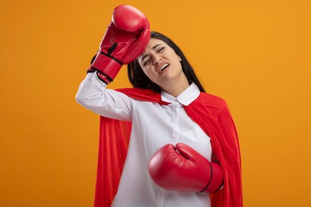 Усталая молодая кавказская девушка-супергерой в боксерских перчатках трогает голову с закрытыми глазами, изолированными на оранжевом фоне с копией пространства