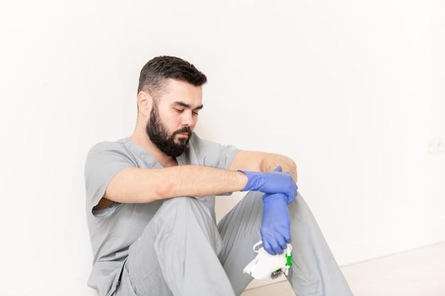 病気の患者との仕事の後、壁のそばの床に座っている間、保護手袋と灰色のユニフォームを持った若い臨床医が疲れている