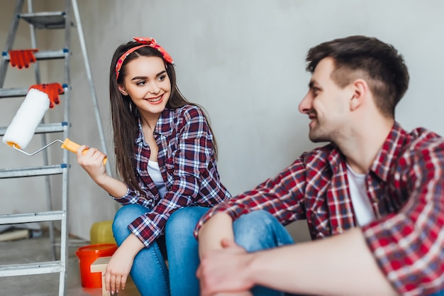 疲れた若いカップルは家で修理をしながらペイントブラシとバケツで床に座っています