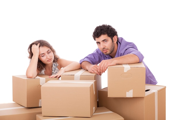 Tired young couple with cardboard boxes