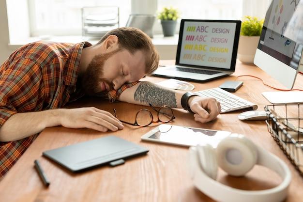 Усталый молодой креативный дизайнер с татуировкой на левой руке дремлет на столе среди гаджетов и других принадлежностей посреди рабочего дня