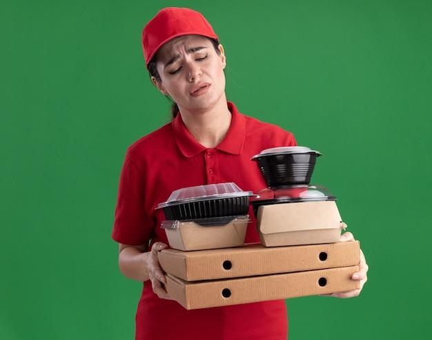 緑の壁に隔離された紙の食品パッケージと食品容器が付いているピザのパッケージを見て制服と帽子を保持している疲れた若い配達の女性
