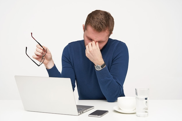 Tired young fair-haired man dressed in blue sweater taking off his eyewear while being exhausted after working with laptop, isolated over white background