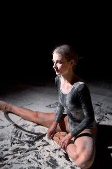 黒の背景にスタジオでトレーニングやパフォーマンスを疲れ果てた後、小麦粉で床に座っているボディスーツの疲れた若い女性のバレエダンサー、才能のある女性のバレリーナはリラックスして座っています。