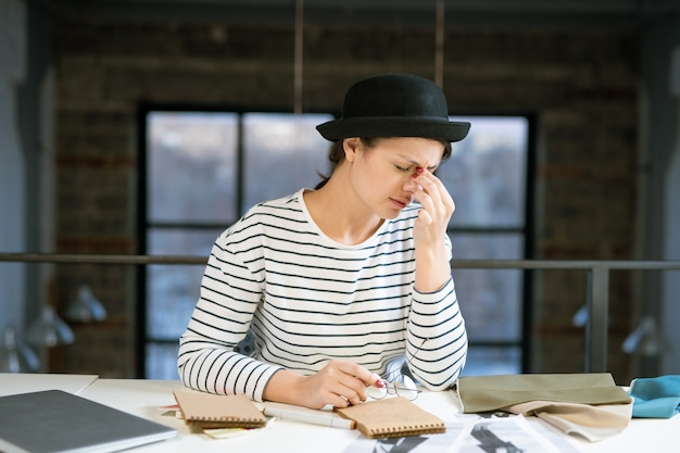 Tired young female designer in hat and striped pullover trying to concentrate while working over new fashion sketches