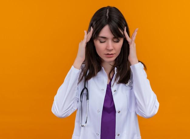 聴診器と医療ローブの疲れた若い女性医師は、コピースペースと孤立したオレンジ色の背景に両手で頭を保持します。