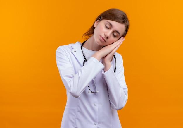 コピースペースのある孤立したオレンジ色の壁で睡眠ジェスチャーをしている医療ローブと聴診器を身に着けている疲れた若い女性医師