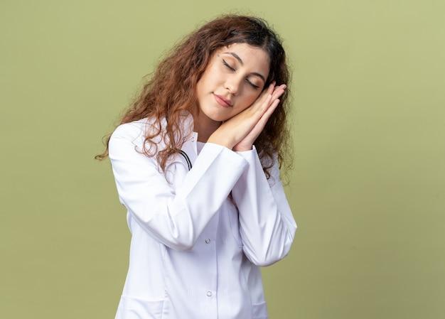 의료 가운과 청진기를 착용하고 복사 공간이 있는 올리브 녹색 벽에 격리된 닫힌 눈으로 잠자는 제스처를 하는 피곤한 젊은 여성 의사