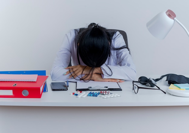 Усталая молодая женщина-врач в медицинском халате и стетоскопе сидит за столом с медицинскими инструментами, положив руки на стол и положив голову на изолированные руки