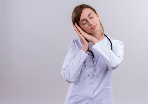 Giovane medico femminile stanco che indossa veste medica e stetoscopio che fa gesto di sonno sulla parete bianca isolata con lo spazio della copia