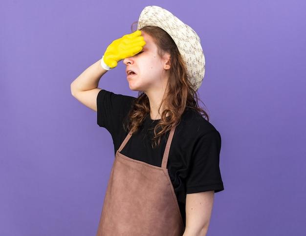 파란 벽에 격리된 손으로 이마를 닦는 장갑이 있는 원예용 모자를 쓴 피곤한 젊은 여성 정원사