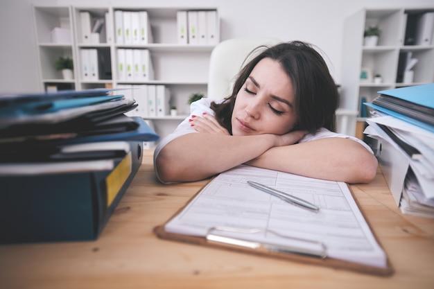 피곤한 젊은 여성 사무실 관리자 또는 회계사가 열심히 일한 후 재정 서류와 함께 클립 보드 앞에서 책상에서 낮잠