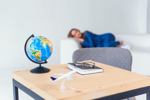 Утомленная молодая студентка в вскользь одежде спит на белой софе. красивая женщина отдыхает после тяжелых учебы или рабочего дня.