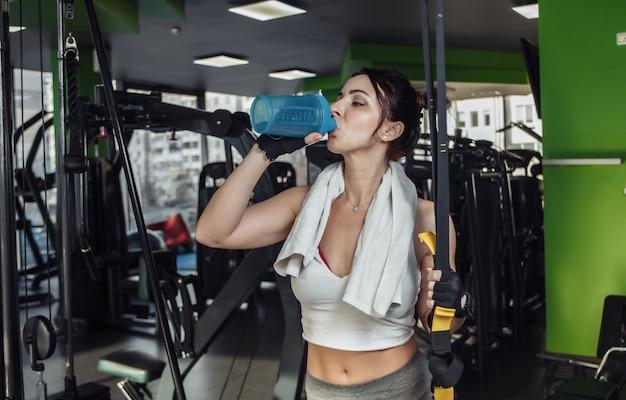 疲れた若いフィットの女性はジムで水を飲む
