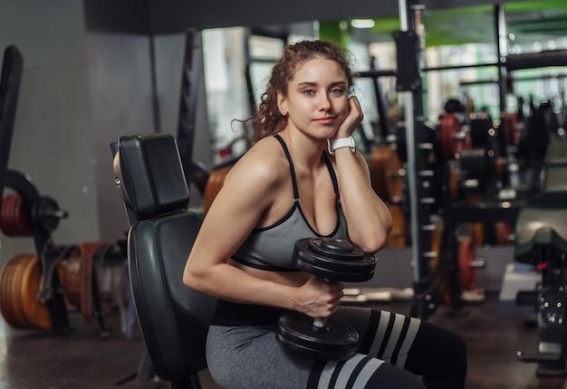 아령을 들고 체육관에서 벤치에 앉아 쉬고 피곤 젊은 맞는 여자
