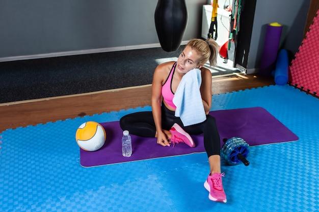 疲れた若いフィットネス女性は、フィットネスクラスのマットに座ってリラックスしながらタオルで汗を拭きます