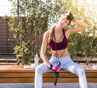 Tired young fitness woman wiping her sweat holding skipping rope around her neck