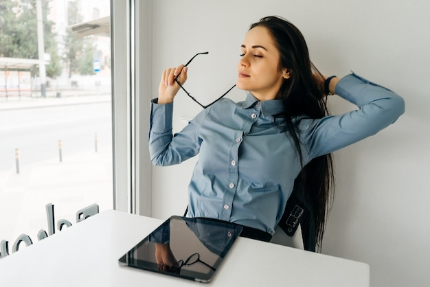 Tired young girl freelancer in a blue shirt working on a tablet