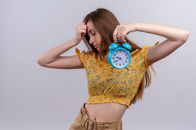 目覚まし時計を保持し、孤立した白い壁に額に手を置く疲れた少女