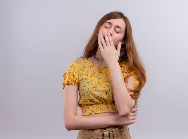 입에 손을 넣고 복사 공간이 격리 된 흰 벽에 닫힌 손으로 하품 피곤 어린 소녀